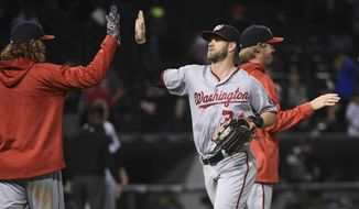 Washington Nationals right fielder Bryce Harper (34) high fives teammates after the Nationals defeated the Chicago White Sox 10-5 in a baseball game in Chicago on Tuesday, June 7, 2016. (AP Photo/Matt Marton)