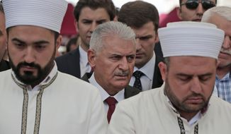 Flanked by imams offering prayers, Turkey's Prime Minister Binali Yildirim attends the funeral procession for two of the victims killed in Tuesday's explosion, at Fatih mosque in Istanbul, Wednesday, June 8, 2016. The bomb attack, targeting a bus carrying riot police during rush hour traffic in Istanbul, has killed a number of people and wounded dozens of others. It marks the fourth bombing to hit the Turkish city this year and there was no immediate responsibility claim but Turkey has witnessed an increase in violence linked to Kurdish rebels and Islamic State militants. (AP Photo/Lefteris Pitarakis)