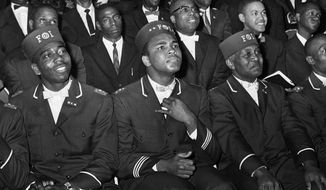 """In this Feb. 28, 1966 photo, Muhammad Ali listens to Elijah Muhammad as he speaks to other black Muslims in Chicago. Two days after the 1964 fight with Sonny Liston, Cassius Clay announced he was a member of the Nation of Islam and was changing his name to Cassius X. He would later become Muhammad Ali as he broke away from Malcom X and aligned himself with the sect's leader, Elijiah Muhammad. """"What is all the commotion about?"""" he asked. """"Nobody asks other people about their religion. But now that I'm the champion I am the king so it seems the world is all shook up about what I believe."""" (AP Photo/Paul Cannon)"""