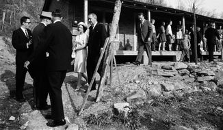 President Lyndon Johnson and his wife, Lady Bird, center left, leave the home in Inez, Ky., of Tom Fletcher, a father of eight who told Johnson he'd been out of work for nearly two years, in this April 24, 1964, photo.  The president visited the Appalachian area in Eastern Kentucky  to see conditions firsthand and announce his War on Poverty from the Fletcher porch.  (AP Photo/FILE)