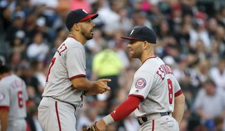 Washington Nationals' Danny Espinosa (8) talks to starting pitcher Gio Gonzalez during the first inning of a baseball game against the Chicago White Sox on Thursday, June 9, 2016, in Chicago. (AP Photo/Charles Rex Arbogast)