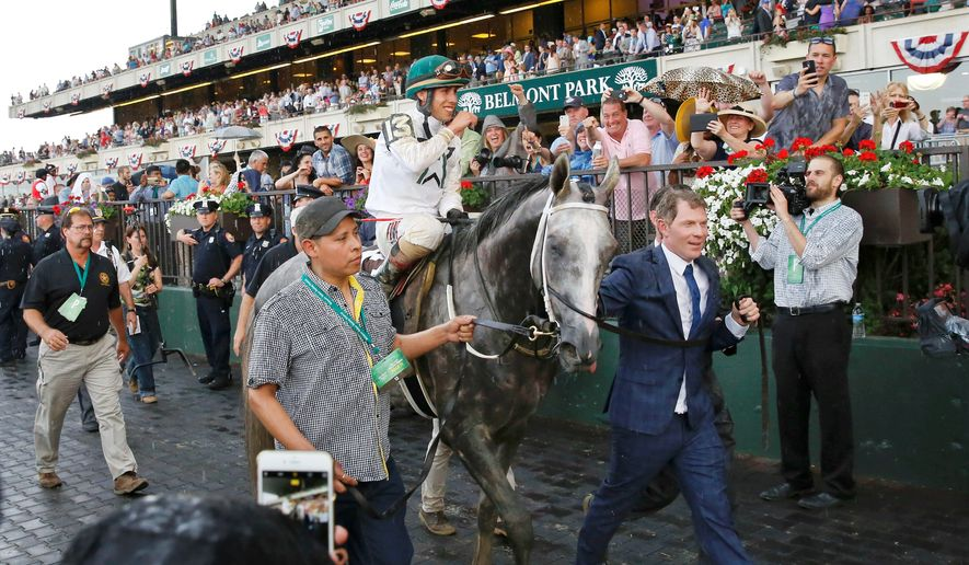 Part owner Bobby Flay (right) leads Creator, with jockey Javier Castellano, into the Winner's Circle, after Creator won the Belmont Stakes on Saturday. (Associated Press)