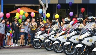 Los Angeles County Sheriff's department motorcycle deputies ride along a street in West Hollywood, Calif., during the Gay Pride Parade on Sunday, June 12, 2016. A heavily armed man arrested in Southern California told police he was in the area for West Hollywood's gay pride parade. (AP Photo/Richard Vogel)