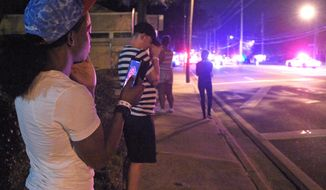 Jermaine Towns, left, and Brandon Shuford, second from left, wait down the street from the scene of a shooting involving multiple fatalities at a nightclub in Orlando, Fla., Sunday, June 12, 2016. Towns said his brother was hiding in a bathroom at the time. (AP Photo/Phelan M. Ebenhack)