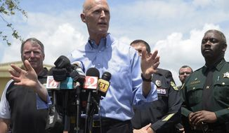 Florida Gov. Rick Scott, center, addresses reporters during a news conference after a shooting involving multiple fatalities at a nightclub in Orlando, Fla., Sunday, June 12, 2016. (AP Photo/Phelan M. Ebenhack)