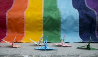 50 origami birds made by Samantha Brouwer and Gabrielle Grace sit around a rainbow flag during a vigil honoring the Orlando shooting victims hosted by the Kalamazoo Gay Lesbian Resource Center in Kalamazoo, Mich. on Monday, June 13, 2016. A gunman has killed dozens of people in a massacre at a crowded gay nightclub in Orlando, Fla. on Sunday, making it the deadliest mass shooting in modern U.S. history.  (Chelsea Purgahn/Kalamazoo Gazette-MLive Media Group via AP) LOCAL TELEVISION OUT; LOCAL RADIO OUT; MANDATORY CREDIT