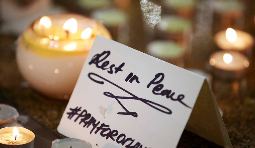 """A note is placed at an impromptu candle-lit memorial set up in Sydney, Monday, June 13, 2016, following the Florida mass shooting at the Pulse Orlando nightclub where police say a gunman wielding an assault-type rifle opened fire, killing at least 50 people and wounding dozens. Australian Prime Minister Malcolm Turnbull said that the Orlando mass shooting was """"an attack on all of us  on all our freedoms, the freedom to gather together, to celebrate, to share time with friends."""" (AP Photo/Rick Rycroft)"""