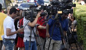 Reporters and photographers gather outside the Beardall Senior Center Monday, June 13, 2016, in Orlando. A steady stream of victim's immediate family made their way to the Beardall Monday, where theyere offered grief counseling and given information about the deadly Pulse Nightclub shooting investigation.  (Chris Urso/Tampa Bay Times via AP)