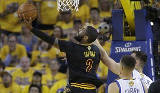 Cleveland Cavaliers guard Kyrie Irving (2) shoots against Golden State Warriors guard Stephen Curry (30) and center Andrew Bogut during the first half of Game 5 of basketball's NBA Finals in Oakland, Calif., Monday, June 13, 2016. (AP Photo/Marcio Jose Sanchez)