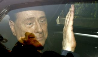 in this Friday, July 18, 2014, file photo, Italy's former Premier Silvio Berlusconi waves as he leaves the 'Sacra Famiglia' institute in Cesano Boscone, Italy. Media mogul Silvio Berlusconi, who served three times as Italian premier, was undergoing heart surgery Tuesday, June 14, 2016 at a Milan hospital. (AP Photo/Luca Bruno, File)
