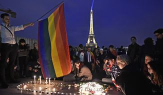 People mourn around candles at the Place Trocadero in front of the Eiffel Tower in Paris, France, to honor victims of Sunday's mass shooting at an Orlando gay club, Monday, June 13, 2016. People brought banners, flags and candles to the Place Trocadero in front of the Paris landmark. (AP Photo/Martin Meissner)