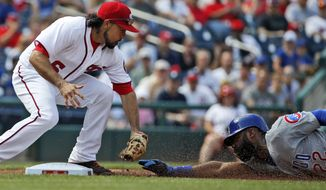 Washington Nationals third baseman Anthony Rendon reaches to tag out Chicago Cubs' Jason Heyward while attempting to steal third base base in first inning Wednesday. (AP Photo/Alex Brandon)