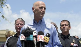 Florida Gov. Rick Scott, center, addresses reporters during a news conference after a shooting involving multiple fatalities at a nightclub in Orlando, Fla., Sunday, June 12, 2016. Listening are Orlando Mayor Buddy Dyer, left, and Orlando Police Chief John Mina. (AP Photo/Phelan M. Ebenhack)