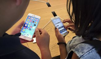 Customers try out Apple iPhone 6S models on display at an Apple Store in Beijing, Saturday, June 18, 2016. (AP Photo/Mark Schiefelbein) ** FILE **