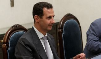 Syrian President Bashar Assad listens to  Russian Defense Minister Sergei Shoigu during their talks in Damascus, Syria, Saturday, June 18, 2016. Russia's defense minister visited Syria on Saturday to meet the country's leader and inspect the Russian air base there, a high-profile trip intended to underline Moscow's role in the region. (Vadim Savitsky/ Russian Defense Ministry Press Service pool photo via AP)