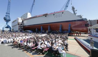 A crowd watches the christening ceremony for the Zumwalt-class guided missile destroyer Michael Monsoor (DDG 1001) Saturday, June 18, 2016 at Bath Iron Works in Bath, Maine. (Joel Page/Portland Press Herald via AP) MANDATORY CREDIT