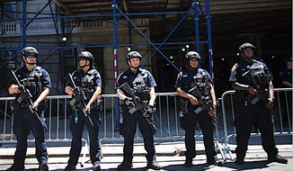 Heavily armed police officers stand at the ready outside a news conference in New York City to address the Orlando terror attack. (Associated Press)