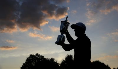 Dustin Johnson holds the trophy after winning the U.S. Open golf championship at Oakmont Country Club on Sunday, June 19, 2016, in Oakmont, Pa. (AP Photo/Charlie Riedel)