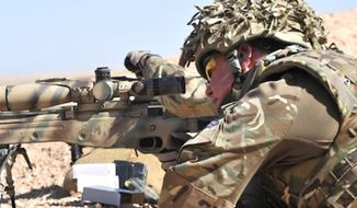 A British sniper looks through the scope of his L115A3 rifle. (British Army)