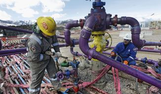 Workers tend to a well head during a hydraulic fracturing operation outside the town of Rifle in western Colorado. (Associated Press) ** FILE **