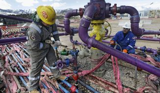 Workers tend to a well head during a hydraulic fracturing operation outside the town of Rifle in western Colorado. (Associated Press)