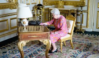 This is a handout photo issued by Buckingham Palace on Tuesday June 21, 2016 of Britain's of Queen Elizabeth II tweeting on a tablet thanking everyone for their birthday messages in the Drawing Room in Windsor Castle, Windsor, England. (Buckingham Palace via AP)