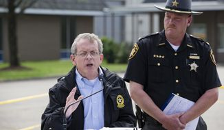 FILE - In this April 27, 2016, file photo, Ohio Attorney General Mike DeWine, left, and Pike County Sheriff Charles Reader, right, discuss the slayings of seven adults and a 16-year-old boy from the Rhoden family found shot April 22, 2016, at four properties near Piketon, Ohio, during a news conference in Waverly, Ohio. DeWine and Reader said Tuesday, June 21, 2016, that more than two dozen investigators are focused on solving the slayings, but refused to reveal how much closer they might be to identifying suspects or a motive, saying they don't want to jeopardize the chance to convict whoever's responsible. (AP Photo/John Minchillo, File)