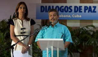 Marco Leon Calarca, member of the FARC, accompanied by Marcela Duran, the Colombian delegation's head of press, speaks about a deal on bilateral cease-fire that would be the last major step toward ending one of the world's longest wars. (Associated Press)