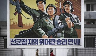 "A North Korean man and woman walk under a mural with a message which reads ""Long live the great victory of the army-first policy"" in the city center of Wonsan on Wednesday, June 22, 2016, in Wonsan, North Korea. (AP Photo/Wong Maye-E)"