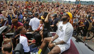 Cleveland Cavaliers' LeBron James, right, sits in the back of a Rolls Royce with his family at the beginning of a parade in downtown Cleveland, Wednesday, June 22, 2016. Cheered by a sea of wine-and-gold dressed fans spilling off sidewalks and choking the streets, LeBron James and the Cavaliers are parading as NBA champions.  (AP Photo/Gene J. Puskar)