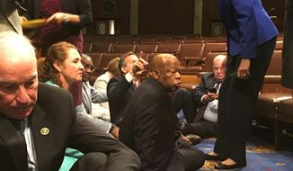 This photo provided by Rep. John Yarmuth, D-Ky., shows Democrat members of Congress, including Rep. John Lewis, D-Ga., center, and Rep. Joe Courtney, D-Conn., left, participate in sit-down protest seeking a a vote on gun control measures, Wednesday, June 22, 2016, on the floor of the House on Capitol Hill in Washington. (Rep. John Yarmuth via AP)
