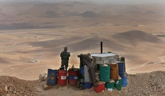 In this Sunday June 19, 2016 photo, a Lebanese army soldier stand guards at one of the frontline hills where they are fighting militants, at the edge of the town of Arsal, on the Syrian border, in northeast Lebanon. The Lebanese army is fighting a war against the Islamic State and al-Qaida and has clawed significant territory back from the extremists. The fighting and shelling near the eastern border town of Arsal occur almost daily. Some 5,000 Lebanese soldiers are fighting against a dwindling number of militants. (AP Photo/Hussein Malla)