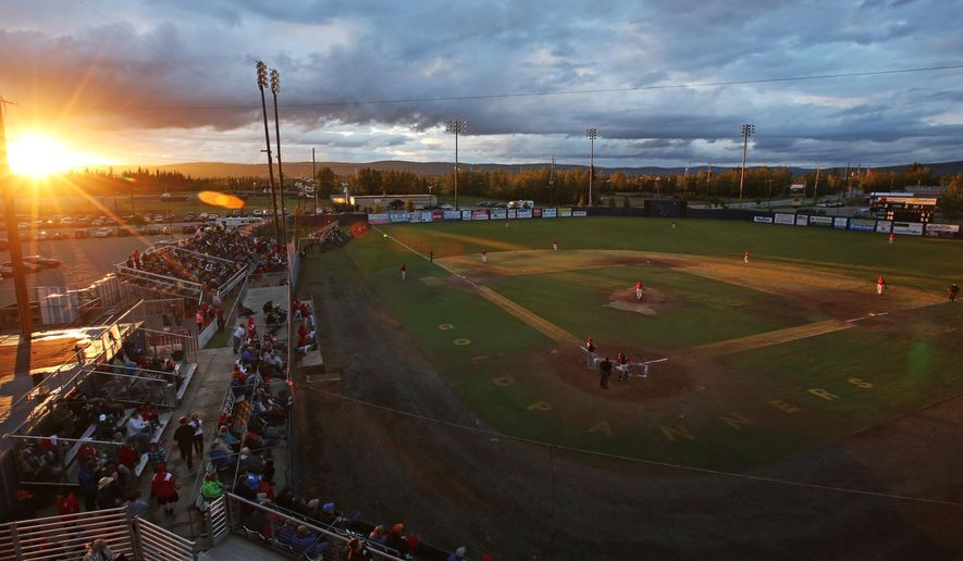 The sun peeks through the clouds above the horizon just before midnight during the 111th Midnight Sun Baseball Game between the Alaska Goldpanners and the Peninsula Oilers Tuesday night, June 21, 2016 at Growden Memorial Park in Fairbanks, Alaska. (Eric Engman/Fairbanks Daily News-Miner via AP) MANDATORY CREDIT