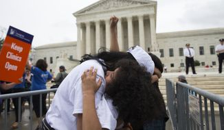 Jackelin Alfaro, 7, of Washington, hugs her aunt Gelin Alfaro, of Veracruz, Mexico, during an immigration rally at the Supreme Court in Washington, Thursday, June 23, 2016. A tie vote by the Supreme Court is blocking President Barack Obama's immigration plan that sought to shield millions living in the U.S. illegally from deportation. The justices' one-sentence opinion effectively kills the plan for the duration of Obama's presidency.  (AP Photo/Evan Vucci)