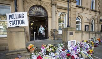 A woman leaves a polling station being used in the EU referendum at Batley Town Hall in west Yorkshire, England in the constituency of murdered Labour MP Jo Cox, Thursday June 23, 2016. Voters in Britain are deciding Thursday whether the country should remain in the European Union. (Danny Lawson/PA via AP)