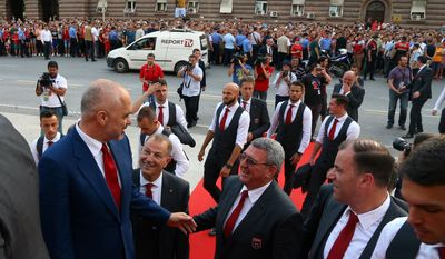 Albanian Prime Minister Edi Rama, left, welcomes the Albanian national soccer squad arriving in Tirana after failing to qualify to the next round at the EURO 2016 European Championship, Thursday, June 23, 2016.(AP Photo/Hektor Pustina)