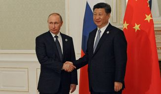 Russian President Vladimir Putin and Chinese President Xi Jinping shake hands during their meeting on the sidelines of the Shanghai Cooperation Organization summit in Tashkent, Uzbekistan, on Thursday. (Associated Press)