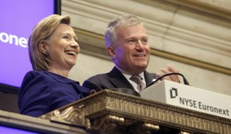 In this Sept. 21, 2009, file photo, then-Secretary of State Hillary Rodham Clinton, rings the New York Stock opening bell, accompanied by then-NYSE CEO Duncan L. Niederauer, in New York. (AP Photo/Richard Drew, File)