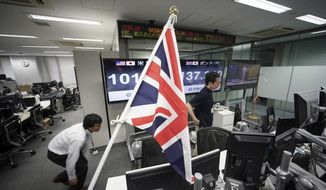 Money traders walk past a flag of the United Kingdom at a foreign exchange brokerage at a securities firm in Tokyo, Friday, June 24, 2016. Global financial markets fluctuated on Friday as votes are tallied in the referendum deciding if Britain is to leave the European Union. (AP Photo/Eugene Hoshiko)