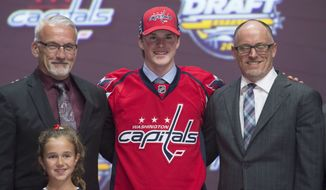 Lucas Johansen stands on stage with members of the Washington Capitals management team at the NHL hockey draft, Friday, June 24, 2016, in Buffalo, N.Y. (Nathan Denette/The Canadian Press via AP)