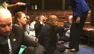 In this photo provided by Rep. John Yarmuth, D-Ky., Democratic members of Congress, including Rep. John Lewis, D-Ga., center, and Rep. Joe Courtney, D-Conn., left, participate in sit-in protest on the floor of the House on Capitol Hill in Washington on Wednesday, June 22, 2016, seeking a vote on gun-control measures. (Rep. John Yarmuth via AP) ** FILE **