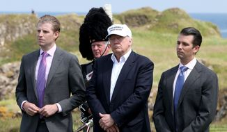 The presumptive Republican presidential nominee Donald Trump, center, with his sons Eric, left, and Donald Trump Jr. during a ceremony at his revamped Trump Turnberry golf course in Turnberry Scotland on Friday, June 24, 2016. (Jane Barlow/PA via AP)