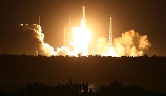 Spectators watch as a Long March 7 (CZ-7) rocket lifts off the launch pad in Wenchang in southern China's Hainan Province Saturday, June 25, 2016. Saturday's launch was the first flight of the 53-meter (174-foot) tall rocket, which also carries a scaled-down version of a new Chinese re-entry capsule for human spaceflight. (Chinatopix via AP) CHINA OUT