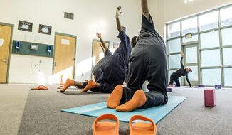 ADVANCE FOR WEEKEND EDTIONS, JUNE 25-26 - In this photo taken May 31, 2016, Alyssa Pizarro, right, leads a yoga session inside a pod at the Remann Hall Juvenile Detention Center in Tacoma, Wash.  The Seattle-based non-profit Yoga Behind Bars teaches yoga to inmates. (David Montesino/The News Tribune via AP)