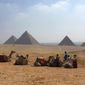 Camels and their riders rest against the backdrop of the pyramids in Giza, Egypt. (Associated Press)