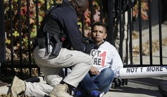A police officer tries to free an immigration protester who chained himself to a gate in front of a building in Atlanta that houses federal immigration offices during a protest on Nov. 19, 2013. (Associated Press) **FILE**