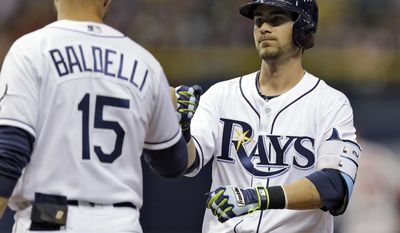 Tampa Bay Rays' Nick Franklin, right, high-fives first base coach Rocco Baldelli after his RBI-single off Boston Red Sox starting pitcher Eduardo Rodriguez scored Oswaldo Arcia during the third inning of a baseball game Monday, June 27, 2016, in St. Petersburg, Fla. (AP Photo/Chris O'Meara)