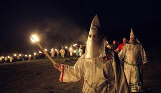 """ADVANCE FOR JUNE 30 -In this Saturday, April 23, 2016 photo, members of the Ku Klux Klan participate in cross burnings after a """"White Pride,"""" rally, in rural Paulding County near Cedar Town, Ga. The Ku Klux Klan is trying to raise its hooded head 150 years after it was founded following the Civil War. Born in the ashes of the smoldering South after the Civil War, the Ku Klux Klan died and was reborn before losing the fight against civil rights in the 1960s. (AP Photo/John Bazemore)"""