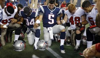 FILE - In this Aug. 16, 2013, file photo, Tampa Bay Buccaneers defensive tackle Gerald McCoy (93), New England Patriots running back Shane Vereen (34), Patriots quarterback Tim Tebow (5), Buccaneers linebacker Joe Holland (49) and Buccaneers quarterback Josh Freeman (5) kneel and pray with others at midfield after an NFL preseason football game in Foxborough, Mass. When a man suffered an apparent heart attack on a flight from Atlanta to Phoenix, Tim Tebow emerged from the first-class section and helped comfort his family. Erik Dellenbach, executive director of the Tim Tebow Foundation, tells the Florida Times-Union that the former NFL quarterback prayed with the family and other passengers after the medical emergency on the Sunday night, June 26, 2016 flight.  (AP Photo/Michael Dwyer, FIle)