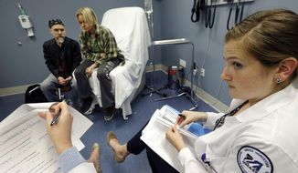 In this May 11, 2016 photo, University of Massachusetts Medical School nursing student Morgan Brescia, right, and others attend a simulation of treatment for a patient coping with addiction during class at the medical school in Worcester, Mass. Many U.S. medical schools are expanding their training to help students fight opioid abuse. New training programs at many schools teach students to prescribe opioid painkillers only as a last resort, and to evaluate all patients for signs of drug abuse. (AP Photo/Elise Amendola)